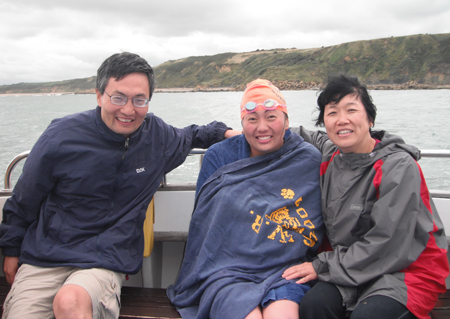 COURTESY PHOTO  |  SWR grad and MIT senior Qing Li wrapped herself in a blanket with her parents by her side after completing a bone-chilling swim across the English Channel.