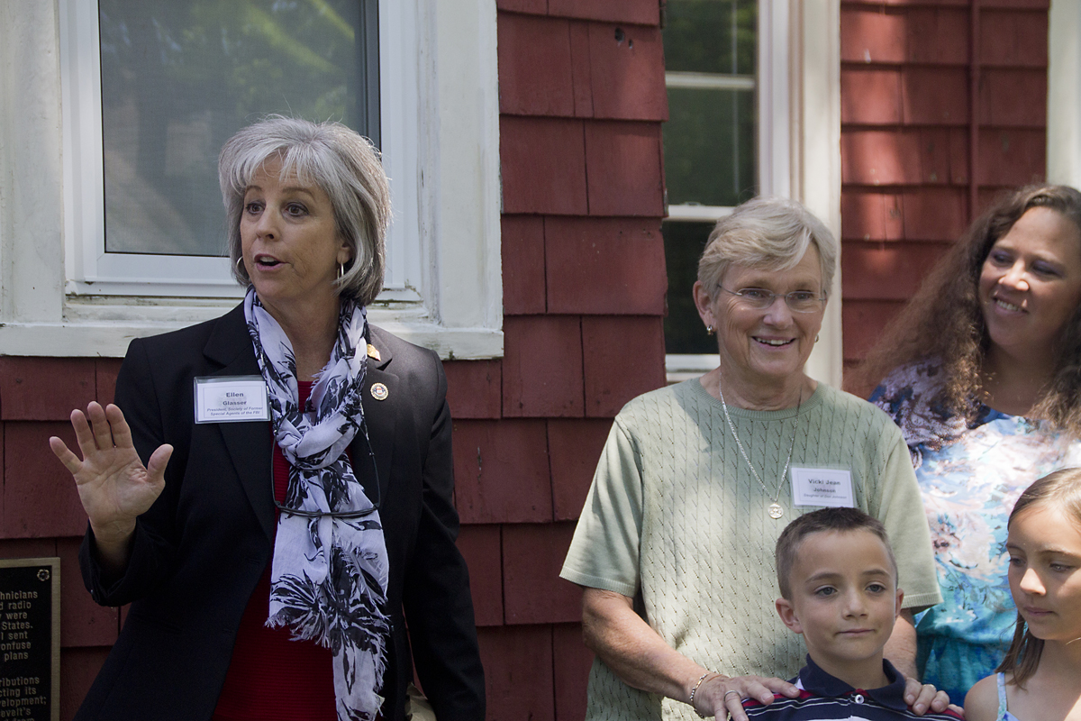 Ellen Glasser, president of the Society of Former Special Agents of the FBI (left), speaks about the Benson House as Vicki Jean Johnson, the daughter of one of the WWII agents (center) watches on. (Credit: Paul Squire)