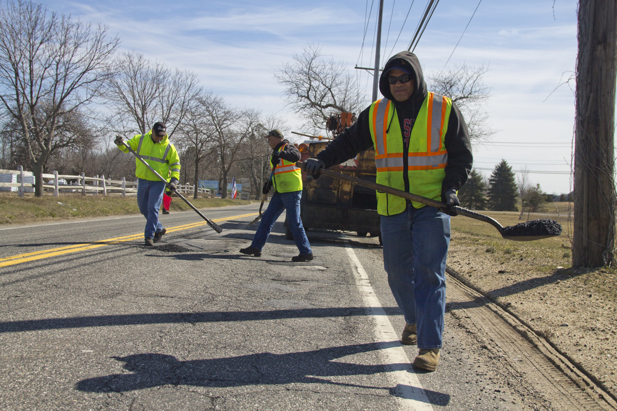 A Riverhead highway crew begins patching up potholes along Sound Avenue Wednesday morning. The workers said this year is the worst they can remember. (Credit: Paul Squire)
