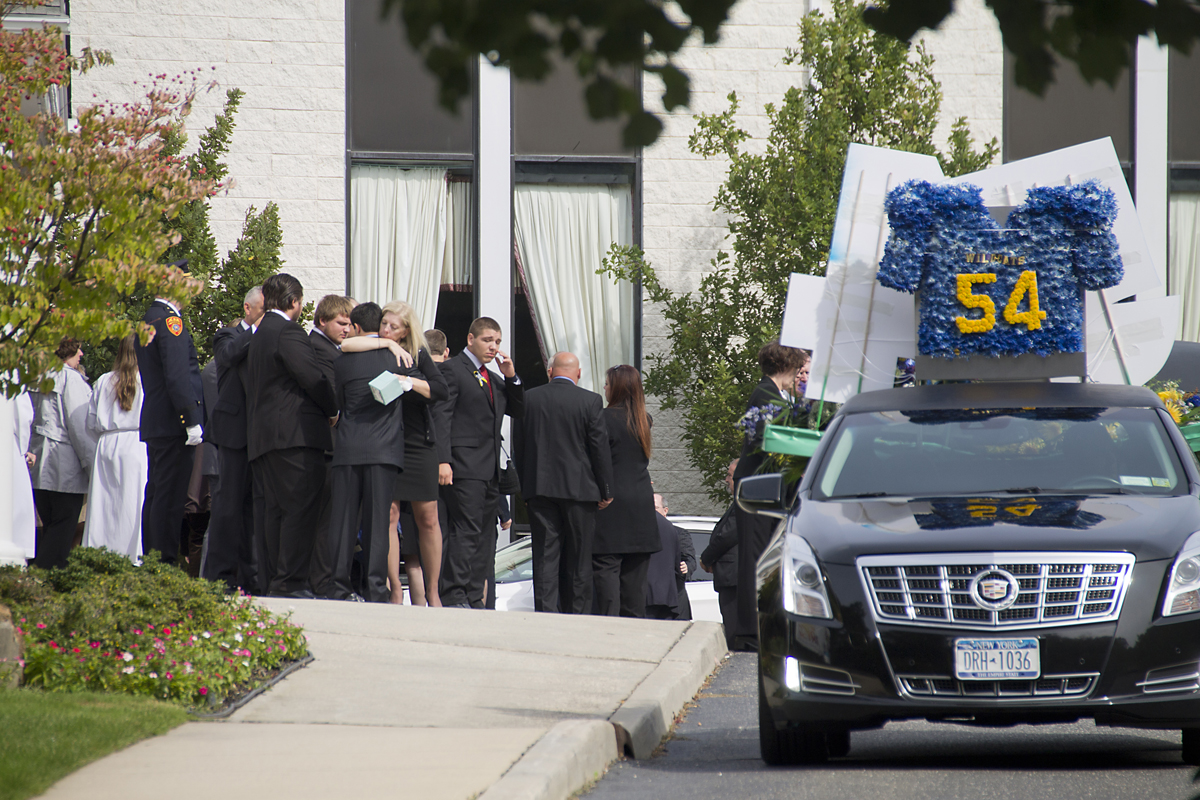 Tom Cutinella's family embrace after the teen's funeral Tuesday morning. The 16-year-old was killed after being injured while playing football last week.