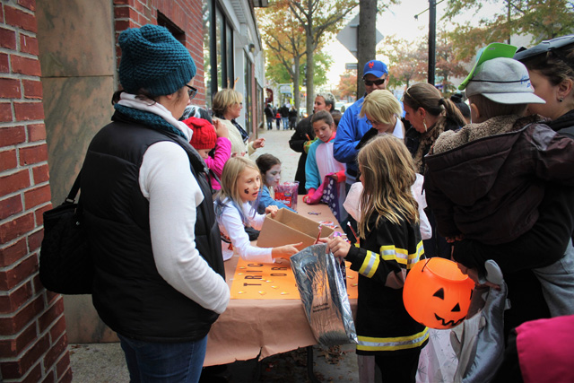 Local Girl Scout Troop 220 distributing Halloween candy to trick-or-treaters in front of the Riverhead Farmer's Market.
