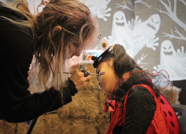 Dawn Miller of Amazing Faces painting a flower on Miso Bang, who dressed as a lady bug for Halloween.