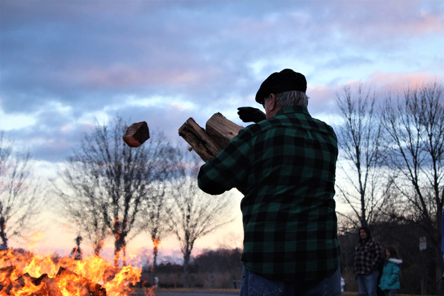 A man tosses another log into the fire. (Credit: Elizabeth Wagner)