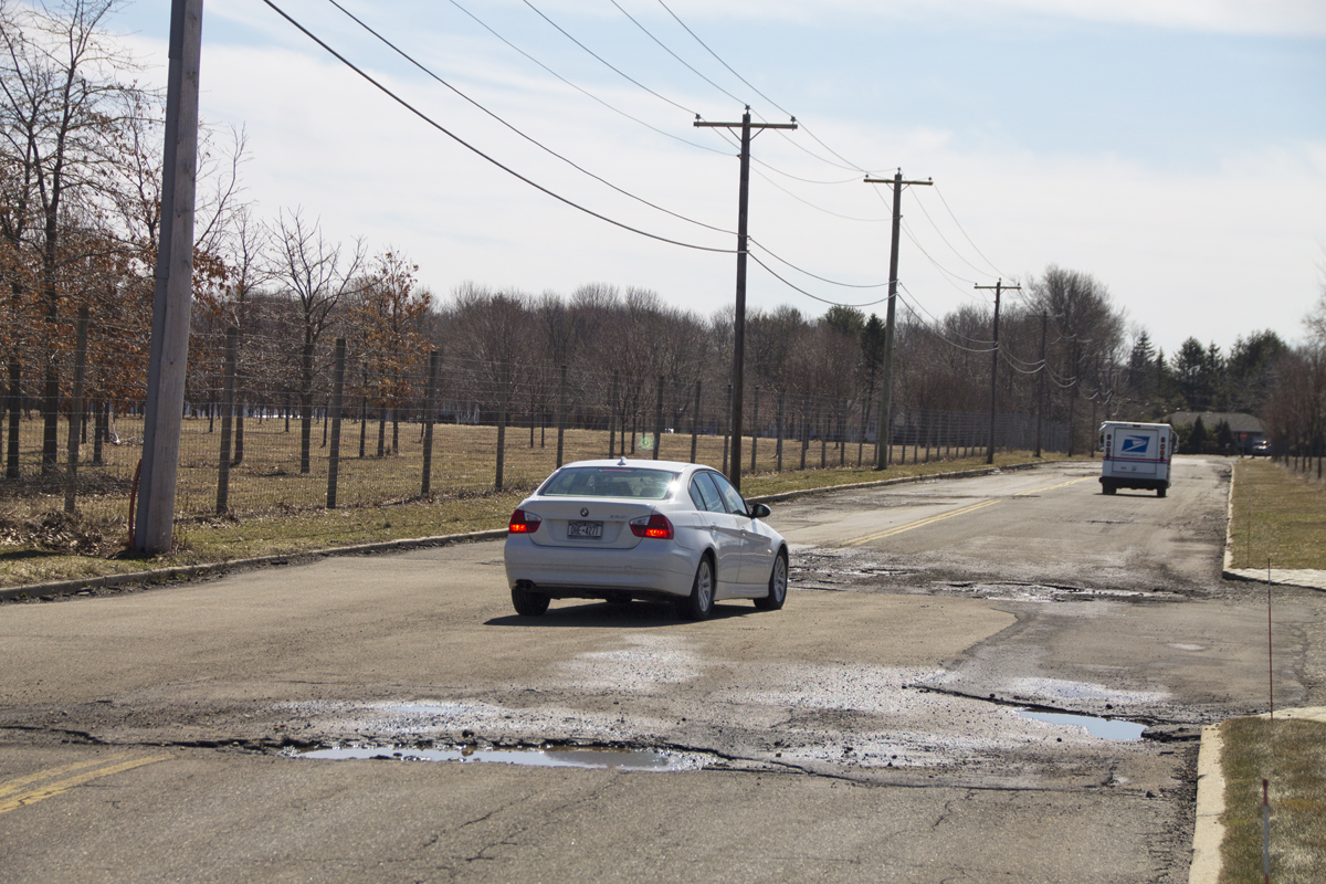 Cars slow down to dodge potholes on Warner Drive in Calverton. (Credit: Paul Squire)