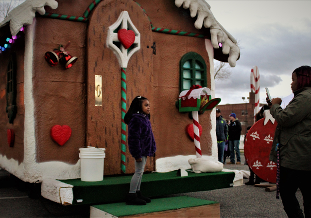 A young girl poses for a photo in front of Santa's Gingerbread House . (Credit: Elizabeth Wagner)