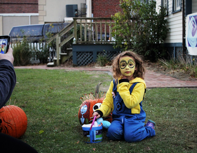 Harmony Orlowski (minion, Port Jefferson Station) posing for a photo with her mother Melissa Orlowski's prize-winning pumpkin. Winners were decided by number of toothpicks inserted into the pumpkin by the public.