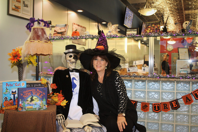 Nancy Kouris (owner of the Blue Duck Bakery Café) posing with the Blue Duck's Halloween mascot, Odin (skeleton) – who is reading a collection of Edgar Allen Poe poems. This is Odin's second Halloween at Blue Duck. He is named for the Norse god Odin, who is the god of war and poetry in Norse mythology.