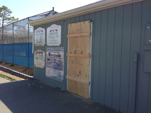 PAUL SQUIRE PHOTO | A Riverhead Town employee boarded up the Little League's storage area Sunday morning after someone broke into the building the night before.