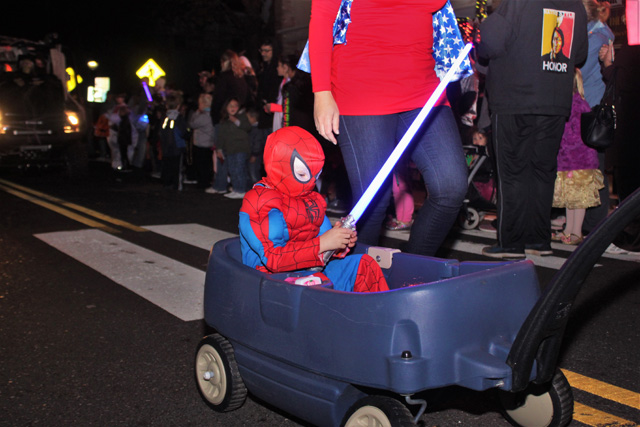 Spiderman with a light saber being towed in the wagon after a long day of trick-or-treating.