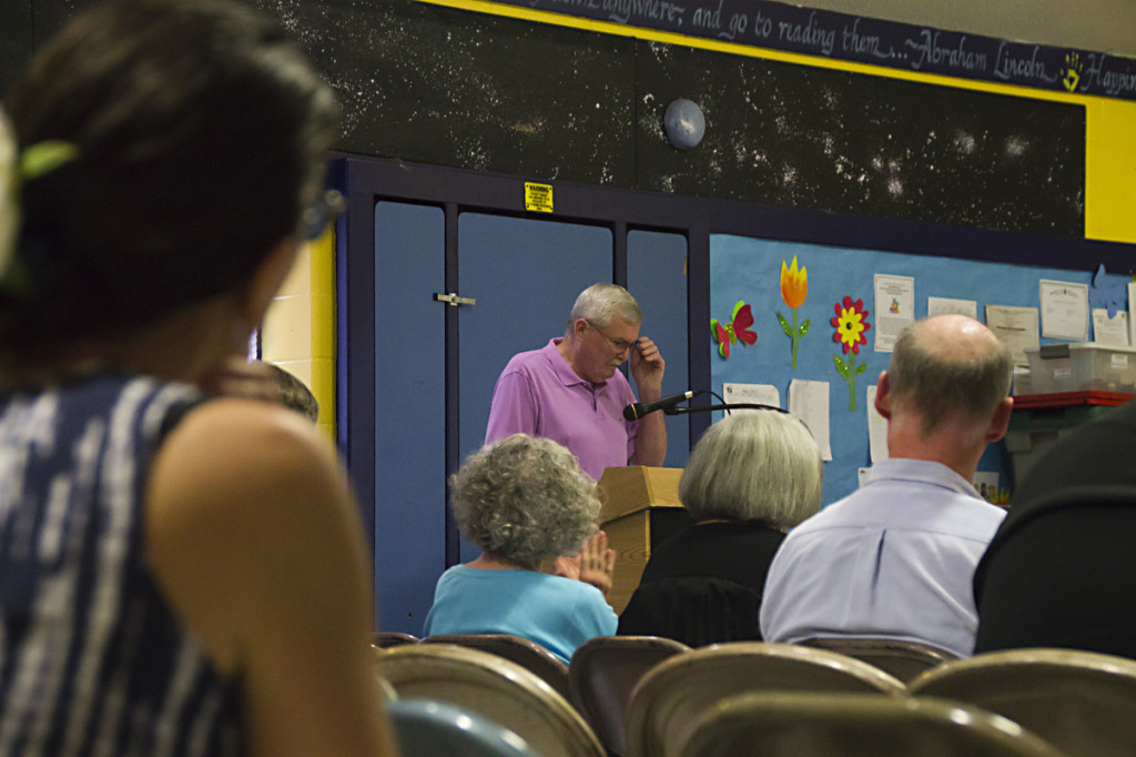 Resident Michael Burns (center) addresses the board last week as neighbors watch on. Mr. Burns was one of a handful to criticize a plan to build a new parking lot. (Credit: Paul Squire)