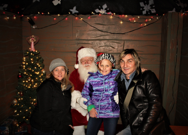 Event organizer and Executive Director of the Riverhead BID, Diane Tucci, posing for a photo with daughter Natalie Tucci, John Golden and Santa. (Credit: Elizabeth Wagner)