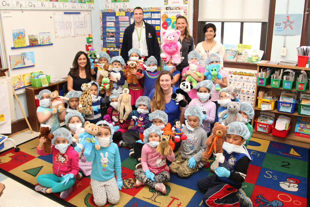 Kindergarten teacher Anselma Jimenez (seated far left with her students) and teacher assistant Marisa Mullane (middle in blue) with their kindergarten students. Also pictured in the back: L-R Dr. Noah Jablow, Kristi Landowski, MPH and Dr. Anupa Dalel from Stony Brook Trauma Center and Hospital.