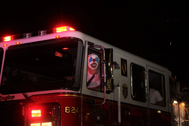 A creepy clown steering the Riverhead Fire Department truck.