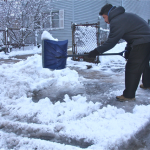 Nery Garcia clears slushy snow from the end of his driveway. (Credit: Barbaraellen Koch)