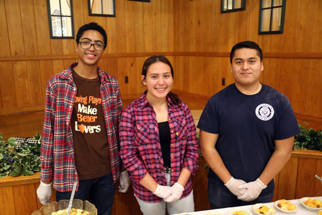 Riverhead High School students Jason Thompson and Roxana Lopez of the Interact Club, from left, with Anthony Muralles of the NJROTC.