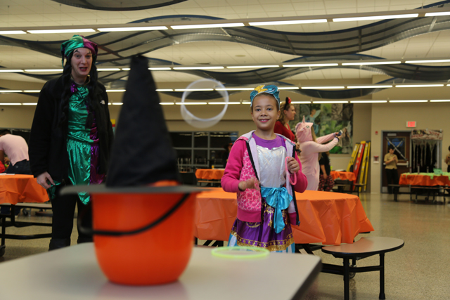Trinity Strand, 7, tosses a ring at the witch's hat in the Riverhead High School spookified cafeteria at Safe Halloween.