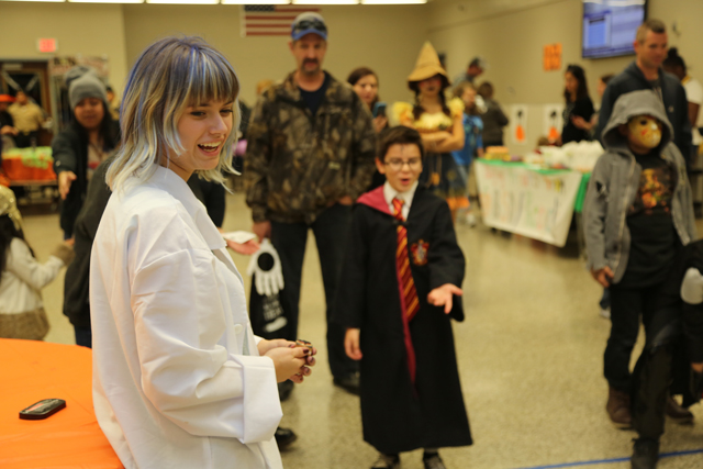 Riverhead High School junior and Key Club president Sarah Brennan watches as 'Harry Potter' knocks over pins in one of the Safe Halloween events.