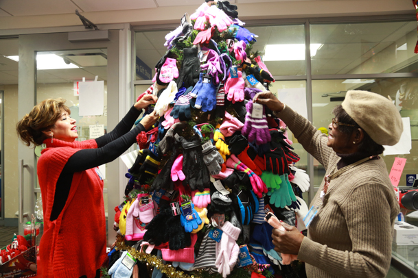 Joan Fehling (left) and Thelma Booker place more donated gloves on the tree on Monday afternoon.