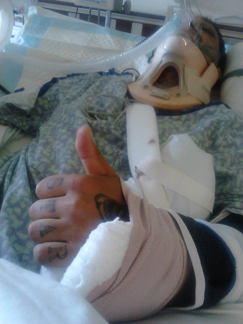 Aaron Hartmann gives a thumbs up from his hospital bed to let friends know he's doing OK. (Credit: Bobby Hartmann file)
