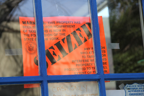 An orange sign on the locked door of Blue Agave Mexican Grill announcing that the restaurant was seized Tuesday afternoon. (Credit: Carrie Miller)