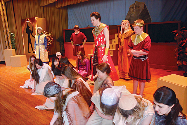Patrick O'Brien of Riverhead as Radames (in red standing), general of the Egyptian army, during the scene with slaves including Aida (front row far right) after she was captured. (Credit: Barbaraellen Koch)