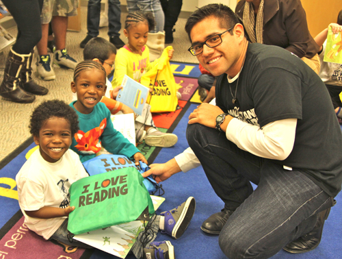 Head Start teacher Kevin Rojas helps distribute books to students at Riverhead Free Library on Thursday. (Credit: Jen Nuzzo photos)