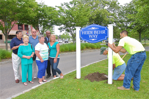HIghway department workers install a street sign last year along the Peconic River in memory of fallen ambulance volunteer Heidi Behr, as the Behr family —  Heidi's grandmother Dorothy, mother June, father John and sister Dana look on. (Credit: Barbaraellen Koch, file)