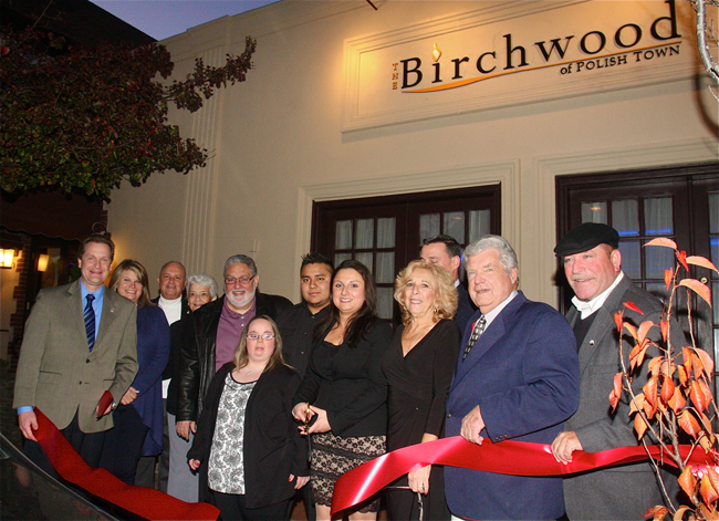 Danielle Sessa (fifth from right) cut the ribbon with family and town officials Monday afternoon to Birchwood of Polish Town. (Credit: Barbaraellen Koch)