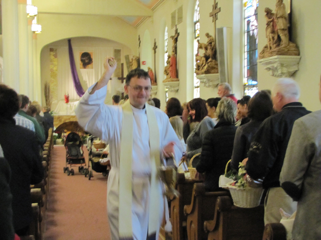 Father Piotr Narkiewicz of St. Isidore Church in Riverhead participates in the annual blessing of the food baskets Saturday morning, an Easter tradition in the Polish church.