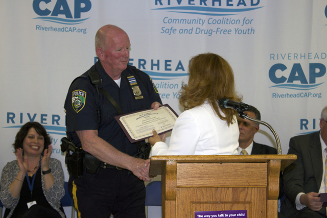 Riverhead Town Police Officer Dennis Cavanagh accepts a certificate on Monday honoring the police department for their efforts in preventing underage substance abuse. (Credit: Nicole Smith)