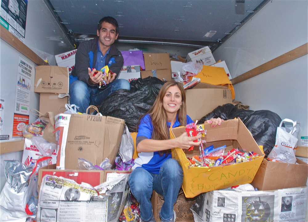 Orthodontist Victor Grazina and his wife and business manager Jennifer Grazina in The U-Haul truck with nearly 5,000 pounds of candy they collected from 31 schools on the North and South Forks.