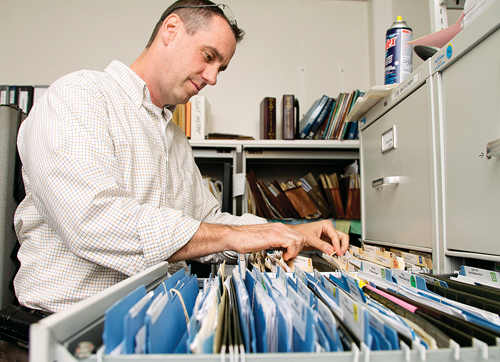 Code enforcement officer Richard Downs goes through some of the files stored in metal cabinets inside the department's office. (Credit: Paul Squire)