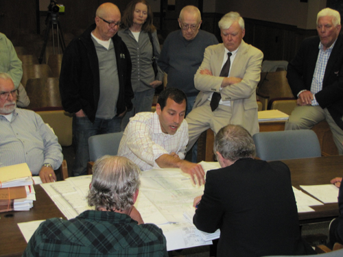 CAPTION: Haig Buchakjian, center, the Senior Vice President of Construction with Brixmor Property Group, promised to make things better at the Costco/Shops at Riverhead development at Thursday's Riverhead Planning Board meeting, while some of the neighbors who have been angered by that development look over his shoulder.