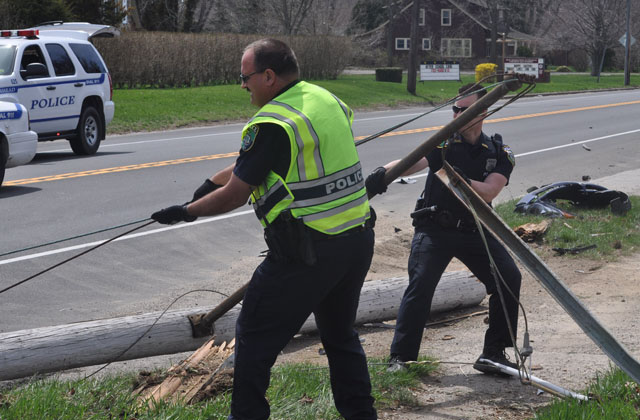 Police work to remove a utility pole from Main Road in Aquebogue after it was struck by a distracted driver. (Credit: Grant Parpan)