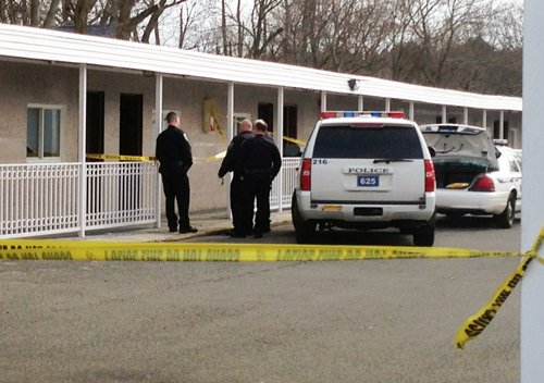 Police investigate outside room 136 of the Greenview Inn on West Main Street in Riverhead.