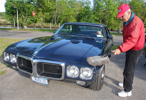 Bill Mango of Aquebogue cleans off his 1969 Pontiac Firebird as his girlfriend Marie Sigother sits in the driver's seat. He bought the car in 1974 and is the second owner. It has 90,000 miles on it. (Credit: Barbaraellen Koch)