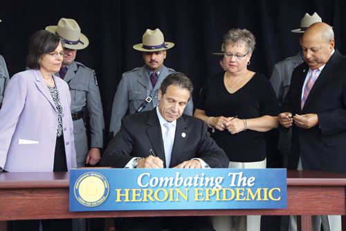 Gov. Andrew Cuomo signs legislation on Monday at the University of Binghampton related to tightening controls on heroin. (Credit: Office of Gov.