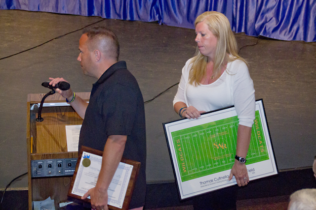Frank and Kelli Cutinella accept a lithograph of the design featuring Thomas' name painted into the field around its center. (Credit: Paul Squire)