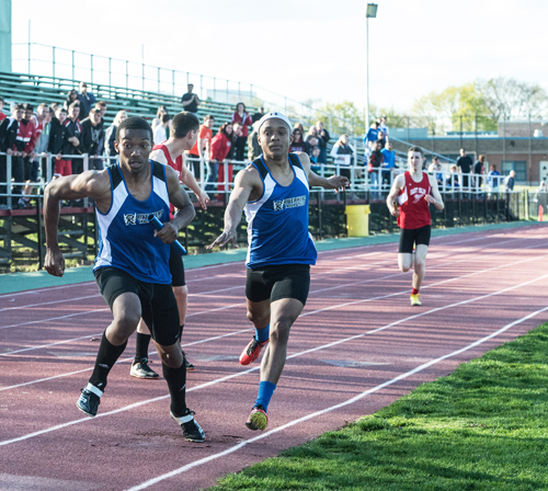 Riverhead's Marcus Moore hands the baton to Davion Porter for the final leg of the 4 x 400 relay Tuesday. (Credit: Robert O'Rourk)