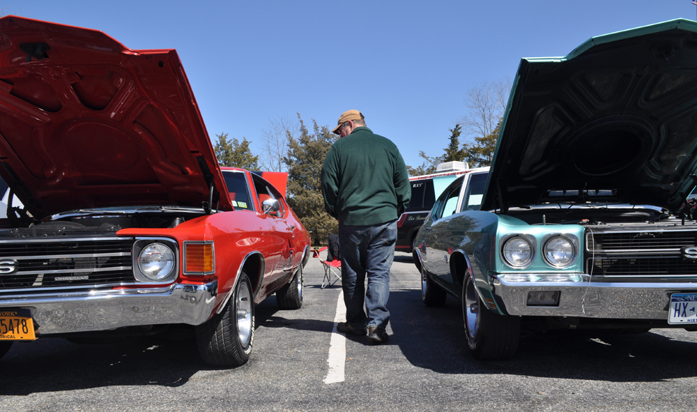 An attendee walks between two Chevys owned by Tobie Wesnofske of Cutchogue. (Credit: Vera Chinese)