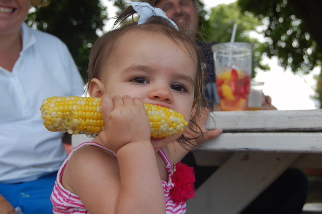 Ashlyn Galante, 2, of Mineola chows down at the Harbes Sweet Corn Festival on Sunday. (Credit: Vera Chinese)