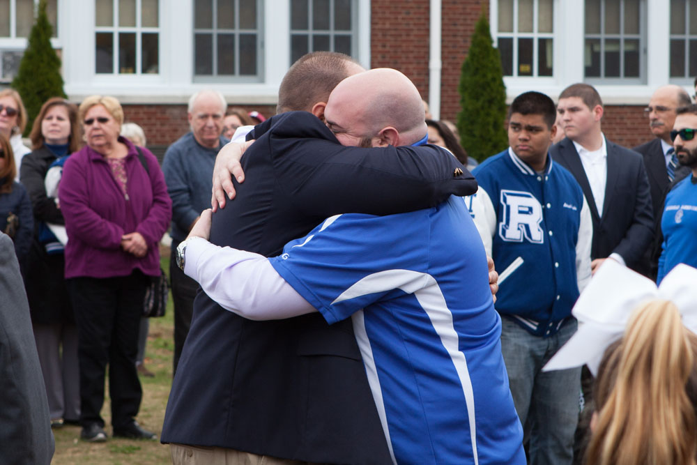 Riverhead football coach Leif Shay hugged each of the DeCabria brothers after they rang the bell. (Credit: Katharine Schroeder)