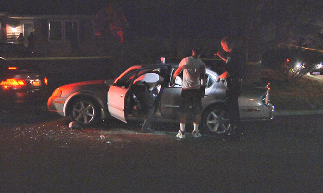 Investigators examine a vehicle at the scene of a shooting in Riverhead Saturday night. (Credit: Stringer News)