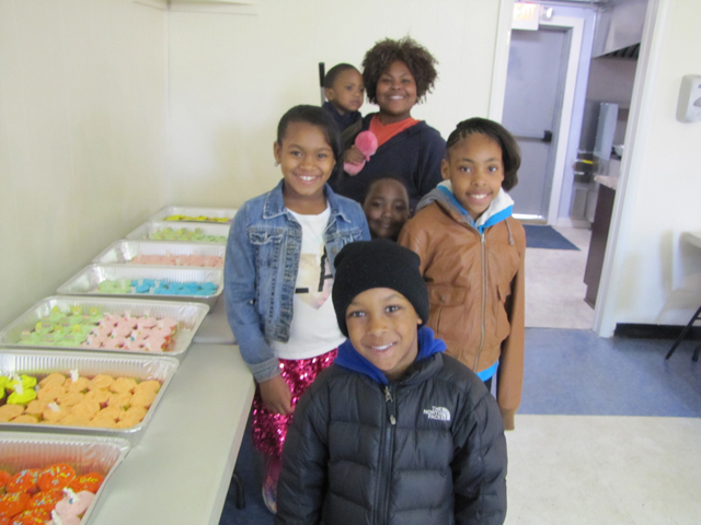 Tyre Lodge Conductress Theodora Midgette, in the back, checking out the cupcakes  with youngsters  Zehki Stephens, Zhirin Stephens (hidden in the middle), Anariynan Williams, Preston Gamble and Egypt Dozier at Saturdays's Easter Egg hunt.