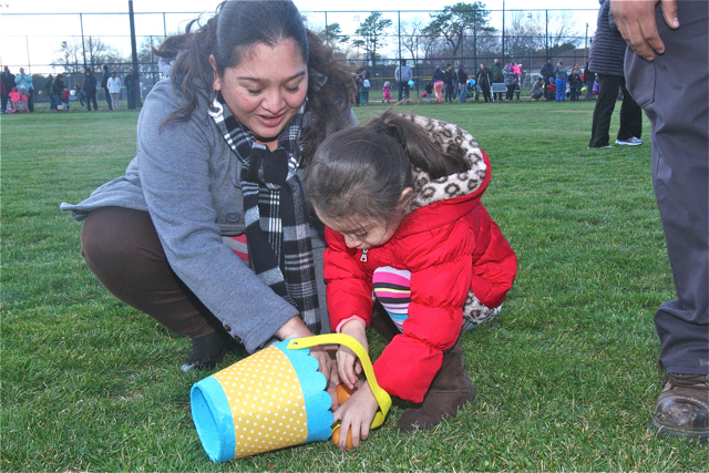 Nassyeli Maldonado and her daughter Giselle, 4, of Riverhead gather eggs. (Credit: Barbaraellen Koch)