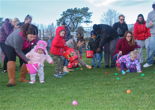 Tina Vasquez (far left) and 1-year-old daughter Alison of Riverhead race to collect eggs. (Credit: Barbaraellen Koch)