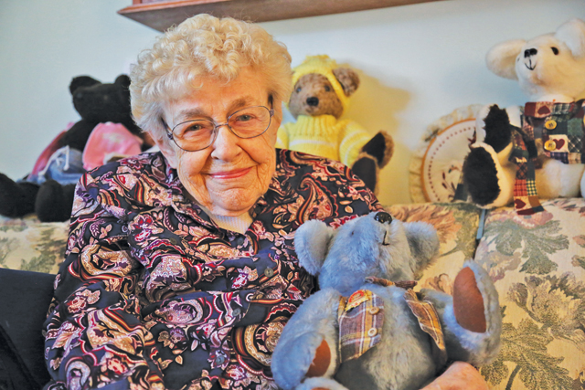 Emily Whitney, 92, sits with her blue stuffed teddy bear, the first stuffed animal she made. (Credit: Paul Squire)