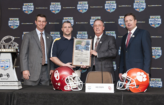 The 2014 Russell Athletic 'Fight Like Dylan Award' is presented to Shoreham-Wading River High School during the 2014 Russell Athletic Bowl Press Conference; L-R, Clemson University head coach Dabo Swinney; Russell Athletic senior vice president, general manager, Robby Davis; Shoreham-Wading High School assistant coach Tom Fabian; University of Oklahoma head coach Bob Stoops. (Credit: Russell Athletic, courtesy)