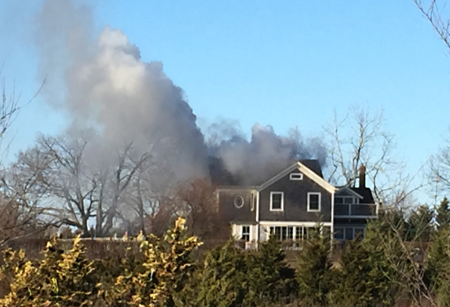 Smoke billowing from a home in Calverton Saturday afternoon. (Credit: Melanie Drozd)