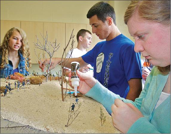 Riverhead High School student Emily Green (right) glues figurines last month on a diorama depicting a battle from the War of 1812. She and Megan Carrick (from left), John Vega, and Brian Brenton were students in Justin Cobis' history class. (Credit: Barbaraellen Koch)